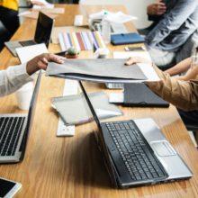 autour d'un bureau, une personne donne une pochette avec un dossier à une autre personne